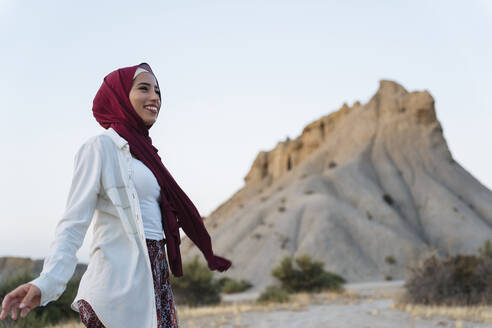 Smiling young tourist woman wearing Hijab in desert landscape - MPPF00991