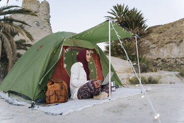Young woman wearing Hijab using laptop at a tent - MPPF00994