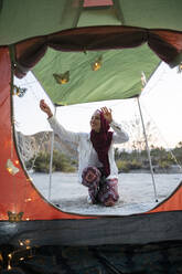 Smiling young tourist woman wearing Hijab decorating a tent - MPPF00997