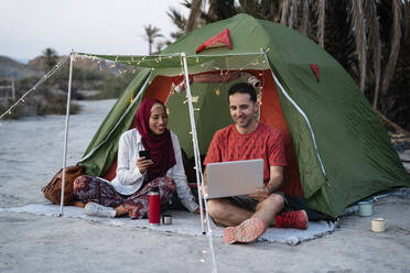 Young woman wearing Hijab and man using laptop at a tent - MPPF01000