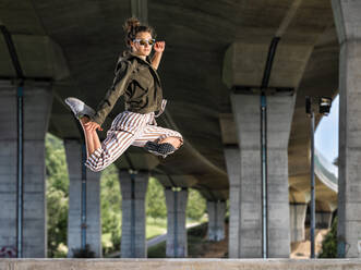 Young womann doing acrobatics and jumping under bridge - STSF02581