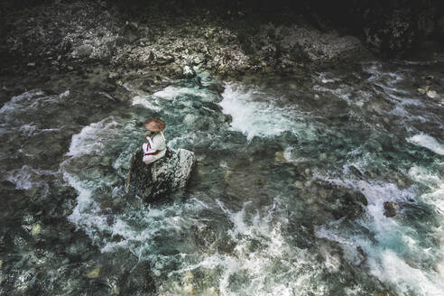 European yamabushi monk sitting on rock in the middle of river and meditating - HMEF01053