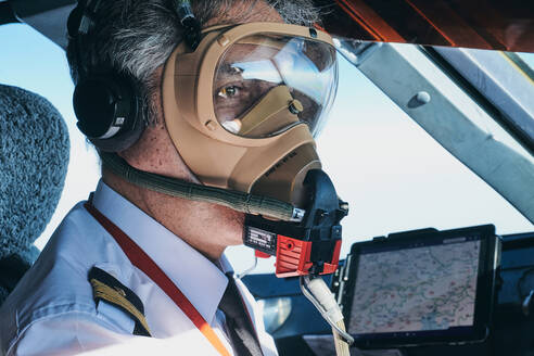 Pilot in mask operating airplane during flight - ADSF09166