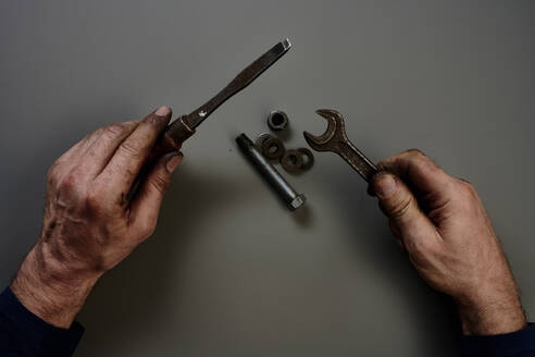 Top view of hand with tools in front of grey background - SRSF00664