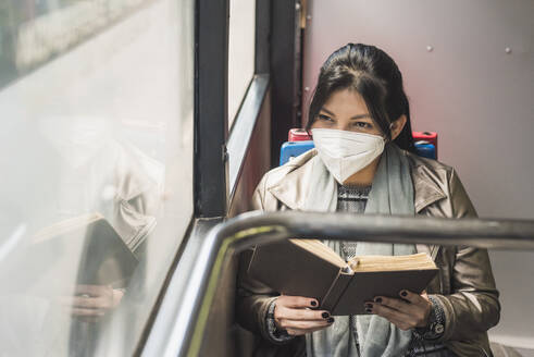 Woman wearing protective mask, looking through window while reading book in bus - DSIF00077