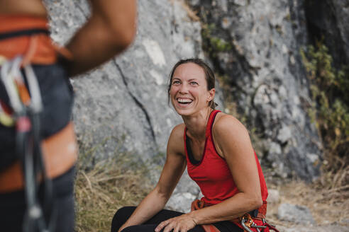 Cheerful female climber looking at friend while relaxing on mountain - DMGF00116