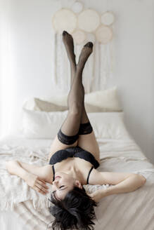 Sensuous woman in lingerie and stockings lying with feet up on bed at home - GMLF00416