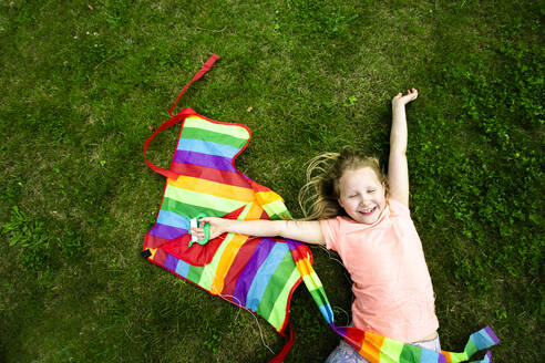Cheerful girl holding kite while lying on grass in park - IHF00378