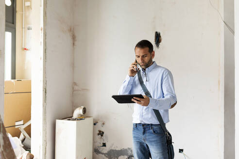 Architect with tablet on the phone in a house under construction - VABF03296