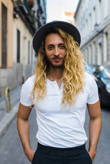 Stylish mid adult man with long hair wearing hat while standing on street in city - JMPF00278