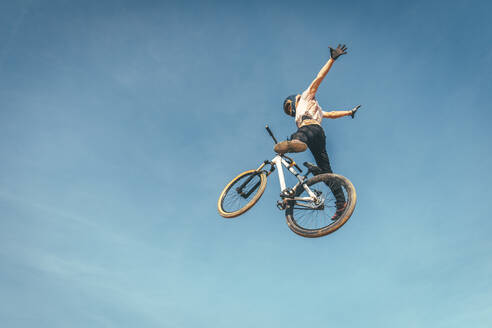 Carefree man performing stunt with bicycle against blue sky during sunset - ACPF00784