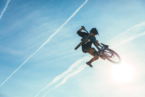 Carefree man jumping while performing stunt with bicycle against blue sky during sunset - ACPF00787