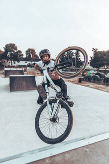 Carefree young man riding bicycle on ramp in park during sunset - ACPF00790