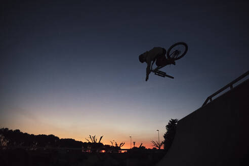 Silhouette young man performing stunt with bicycle against clear sky during sunset - ACPF00799