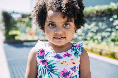 Close-up portrait of cute baby girl with curly hair standing outdoors - MEUF01933