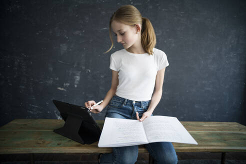 Blond girl learning and using tablet at home - DKOF00026