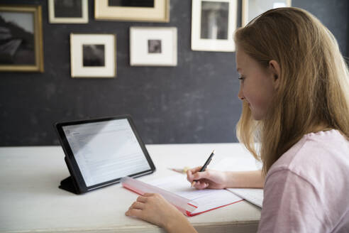 Blond girl learning and using tablet at home - DKOF00035