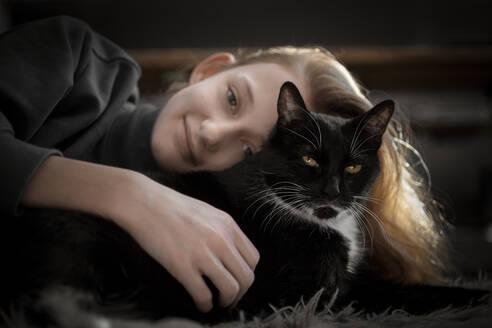 Girl cuddling with black cat - DKOF00041