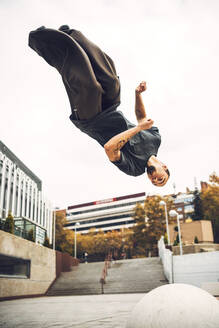 Young man jumping upside down against clear sky - EHF00757