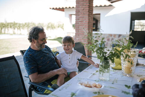 Grandfather and grandchild sitting on chair at dinning table outside house - GRCF00304