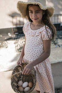 Girl holding wicker basket with freshly laid eggs - GRCF00310
