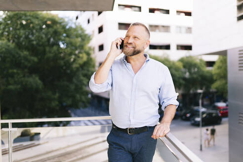Smiling businessman talking on mobile phone while standing at office balcony - DGOF01194