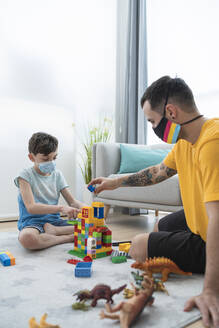 Man and boy wearing masks while playing with toy blocks in living room during Covid-19 quarantine - SNF00469