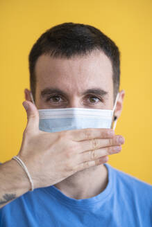 Close-up of mid adult man wearing mask covering mouth with hand against yellow background - SNF00481