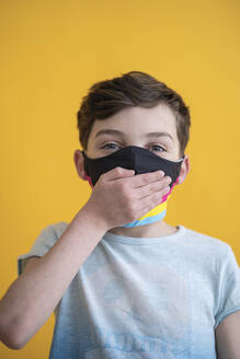 Close-up of boy wearing mask covering mouth with hand against yellow background - SNF00484