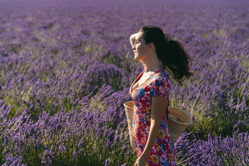 Portrait of beautiful woman standing in vast lavender field with hand in hair - GEMF03975