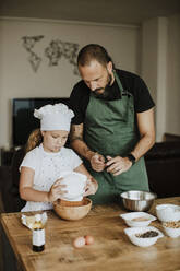 Father and daughter baking cookies at home - GMLF00420