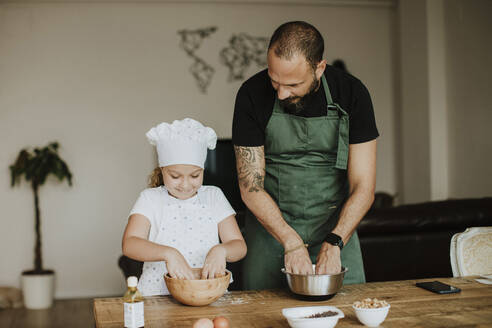 Father and daughter baking cookies at home - GMLF00423