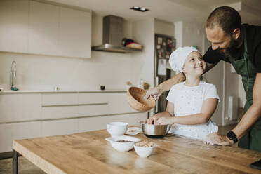 Father and daughter baking cookies at home - GMLF00426