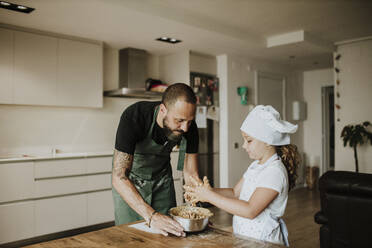 Father and daughter baking cookies at home - GMLF00432