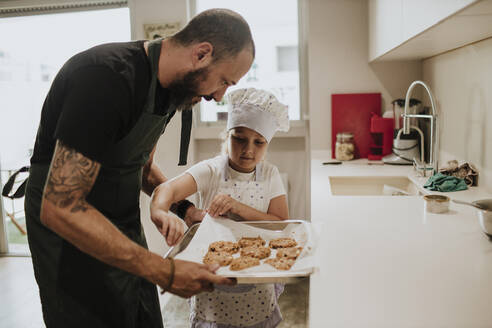 Father and daughter baking cookies at home - GMLF00435