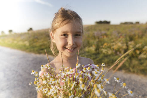 Close-up of smiling girl holding flowers on road against sky at sunset - KMKF01437