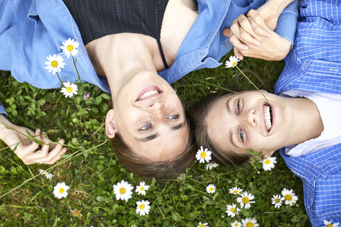 Close-up of cheerful female friends lying by flowers on grassy land in garden - UKOF00059