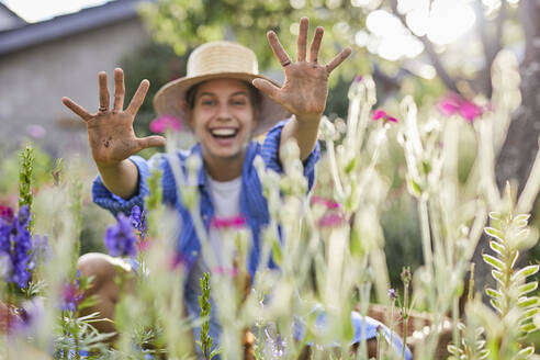 Cheerful woman wearing hat showing dirty hands while sitting amidst plants in garden - UKOF00068