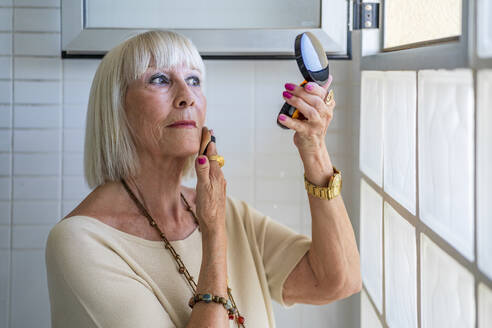 Close-up of senior woman applying face powder while looking in mirror at home - DLTSF01044