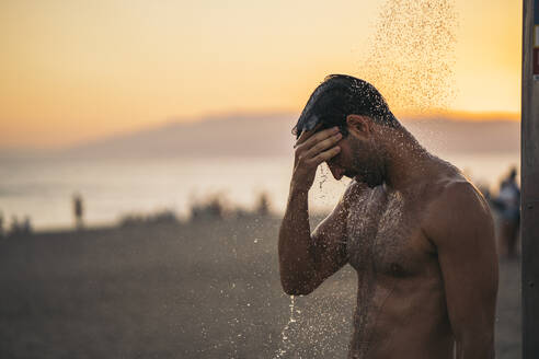 Shirtless man taking shower at beach against sky during sunset - MPPF01016