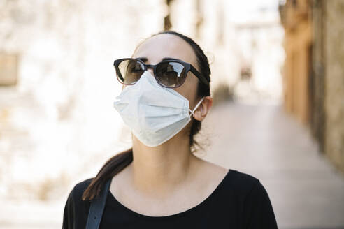Portrait of woman with sunglasses and protective mask in city - XLGF00440