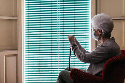 Elderly woman in protective mask and gloves with walking stick sitting near window - ADSF09692