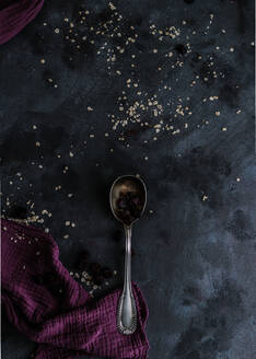 Top view of silver spoon with dried black currant placed on table with kitchen towel and sprinkled oatmeal - ADSF09916