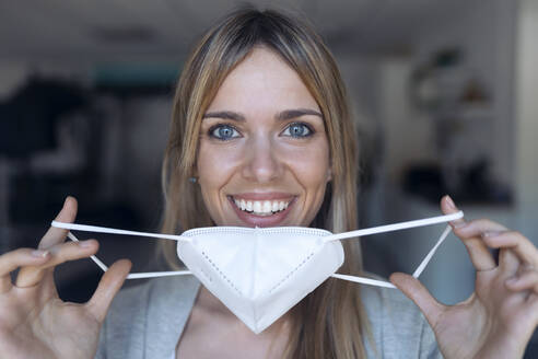 Portrait of smiling young woman putting on protective mask - JSRF00982
