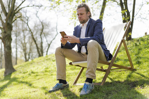 Male entrepreneur using smart phone while sitting on chair at park - JOSEF01441