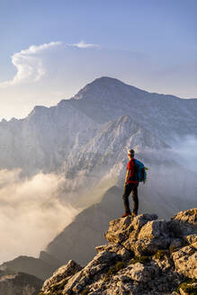 Hiker standing on a mountain peak during golden hour, Orobie Alps, Italy - MCVF00559
