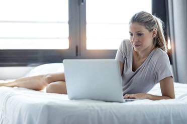 Blond woman using laptop at home - JSRF00986