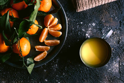 Top view of mug with fresh fruit juice and plate with ripe tangerines placed on rough black table near napkin - ADSF10403