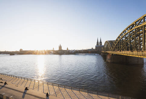 Germany, North Rhine-Westphalia, Cologne, Sun setting over Rhine with Hohenzollern Bridge and Cologne Cathedral in background - GWF06709