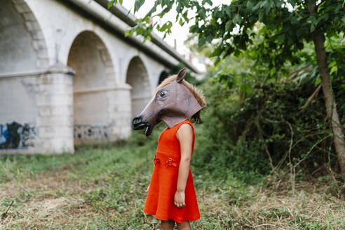 Little girl with a horse's head and a red dress standing  in nature under a bridge - EGAF00645